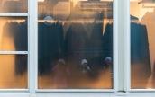 Foto: Eli Kristin Hårberg | Tittel: På utstilling | Sted: Gaubekveita | Tre fotovenner speiles i ruta. Synes fargene i bildet ble fine. Den gule ruta skjuler delvis hva som er på innsiden… vi kan anta at det muligens er et kleslager.