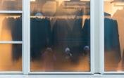 Foto: Eli Kristin Hårberg   Tittel: På utstilling   Sted: Gaubekveita   Tre fotovenner speiles i ruta. Synes fargene i bildet ble fine. Den gule ruta skjuler delvis hva som er på innsiden… vi kan anta at det muligens er et kleslager.