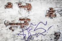 """Foto: Nina Tranø   Tittel: ?es   Sted: Brattørveita (bakgård)   Deler av murpussen hadde falt av og tatt med seg deler av graffitibudskapet. Optimist som jeg er velger jeg å tro at det en gang stod """"Yes""""!"""
