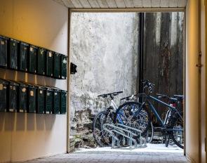 Foto: Liv Stadsøy | Tittel: Bakgård | Sted: Taraldsgårdsveita | En dag jeg gikk bortover Taraldsgårdsveita så jeg for første gang at porten sto åpen i nr. 7, og jeg så inn i en bakgård med mange postkasser og sykler.
