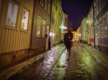Foto: Anne Katharine Dahl | Tittel: Kveld i Taraldsgårdsveita | Sted: Taraldsgårdsveita | Ute er det kaldt regn. Men bak vinduene i Taraldsgårdsveita er det mytji lys og mytji varme.