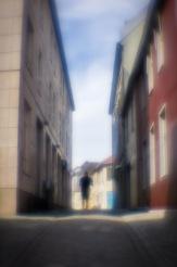 Foto: Linh Hoang   Tittel: A quiet back street   Sted: Brattørveita   Seriebilder av Brattørveita. Kontrasten mellom de høye og store bygningene og mennesker. Farger på bygningene, lys og skygger bidrar til en hyggelig stemning. Får en følelse av å dette er en bakgate fra en storby som f.eks. Spania.