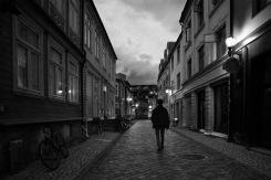 Foto: Anne Vognild Einum | Tittel: Til studenthybelen | Sted: Taraldsgårdsveita | Taraldsgårdsveita med sine forseggjorte vinduer og dører i den lange og idylliske trehusrekka. Det er fadderuke i Trondheim. Studenter ved NTNU hjelper nye studenter til en god studiestart. Denne augustkvelden er det god stemning i veita, og en kan høre glad latter og prat fra åpne vindu.