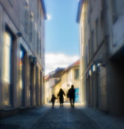Foto: Linh Hoang   Tittel: To the city   STed: Brattørveita   Seriebilder av Brattørveita. Kontrasten mellom de høye og store bygningene og mennesker. Farger på bygningene, lys og skygger bidrar til en hyggelig stemning. Får en følelse av å dette er en bakgate fra en storby som f.eks. Spania.